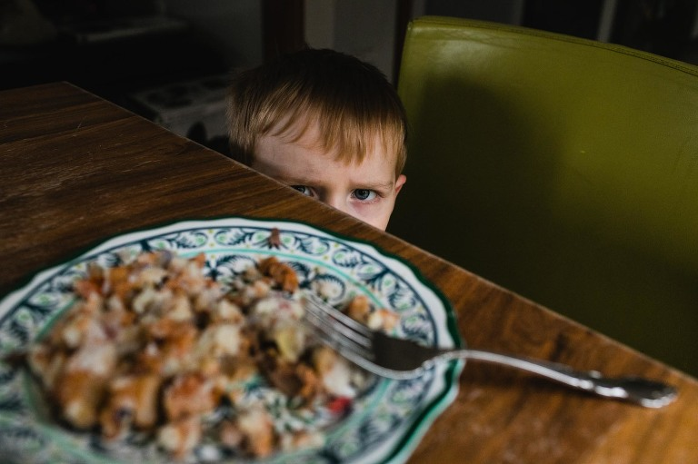 toddler boy refuses to eat his healthy dinner. he gives the camera the evil eye, with his meal in the foreground on the table.
