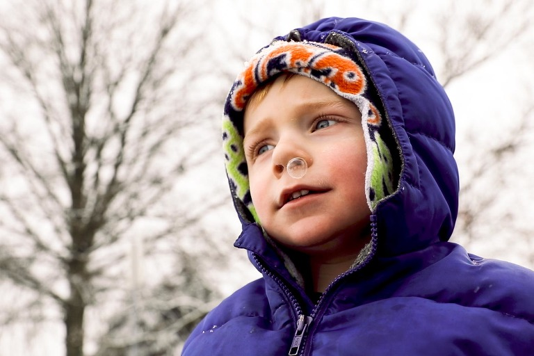 baby toddler in snowsuit outside blows bubble of snot from his nose