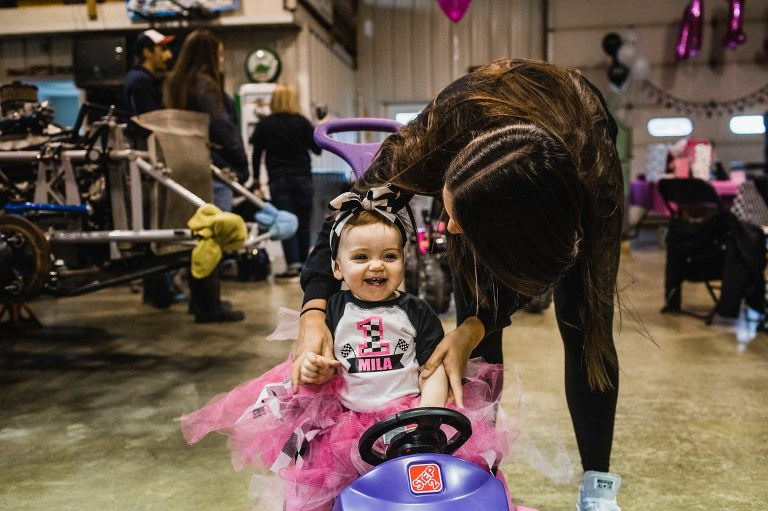 little girl giggling and smiling riding kids car, wearing pink tutu on her first birthday