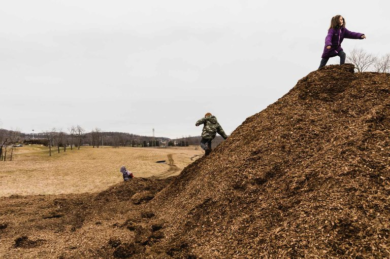 kids run up and down a giant mud pile in the country.