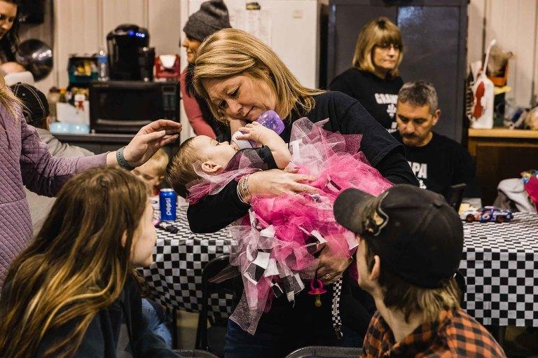 grandma cradling baby girl in her arms, looking into her eyes as she drinks her bottle.