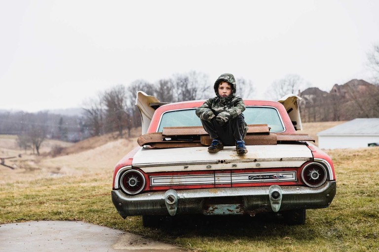 little boy dressed in camp coat on a winter day sits on old vintage car parked in the country.