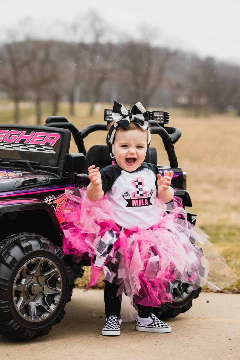 portrait of little girl on her first birthday, wearing a pink tutu and standing in front of a child's size atv.