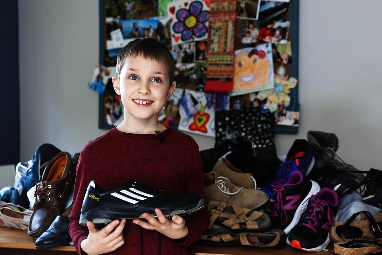 young boy holds sneaker in his hands, while standing in front of a pile of shoes that he has collected