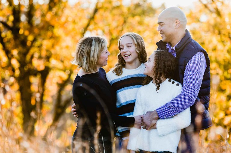 family of four with two teenage girls laughs together surrounded by fall foliage.