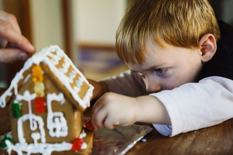 toddler boy carefully puts candy on a gingerbread house he is making