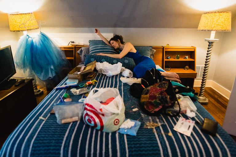 bridesmaid falls asleep on a bed, surrounded by wedding paraphernalia on her friend's wedding day at choderwood