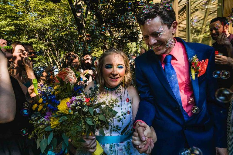 bride and groom exit their outdoor wedding ceremony, surrounded by bubbles from their guests