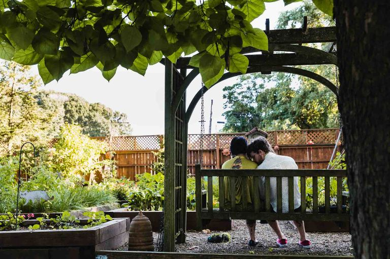 wedding guests sitting on bench in choderwood venue garden lean in to each other and he gives her a kiss on her forehead.
