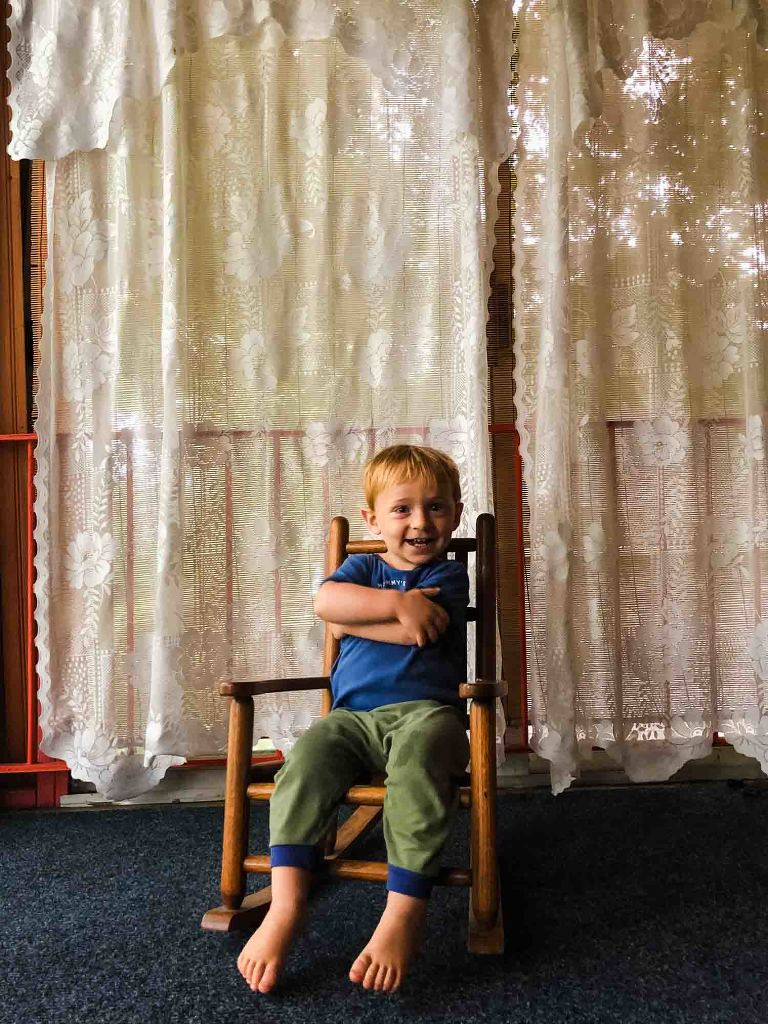 little boy with red hair crosses his arms, sitting in a little rocking chair in front of antique lace curtains