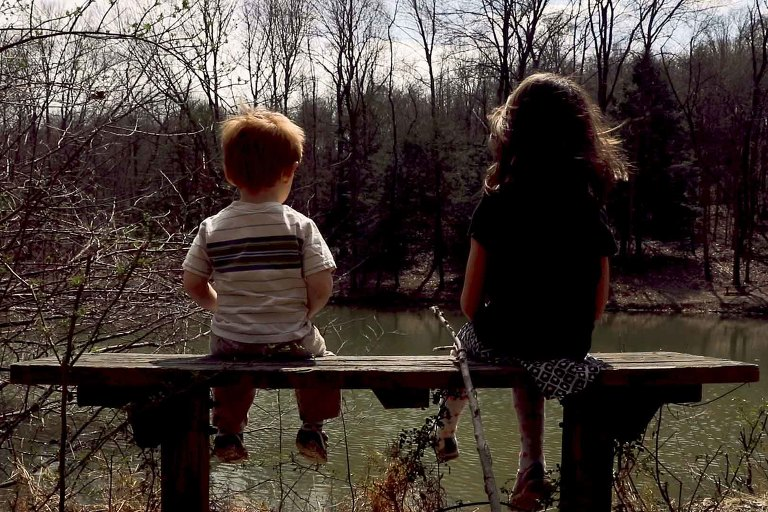 two kids sit on bench with feet dangling, looking out at potter pond, wind blowing in their hair