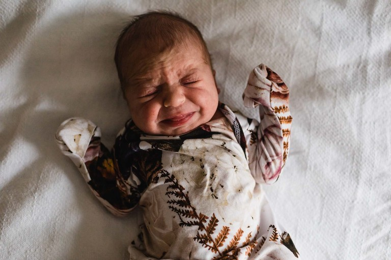 crying newborn baby girl on a blanket