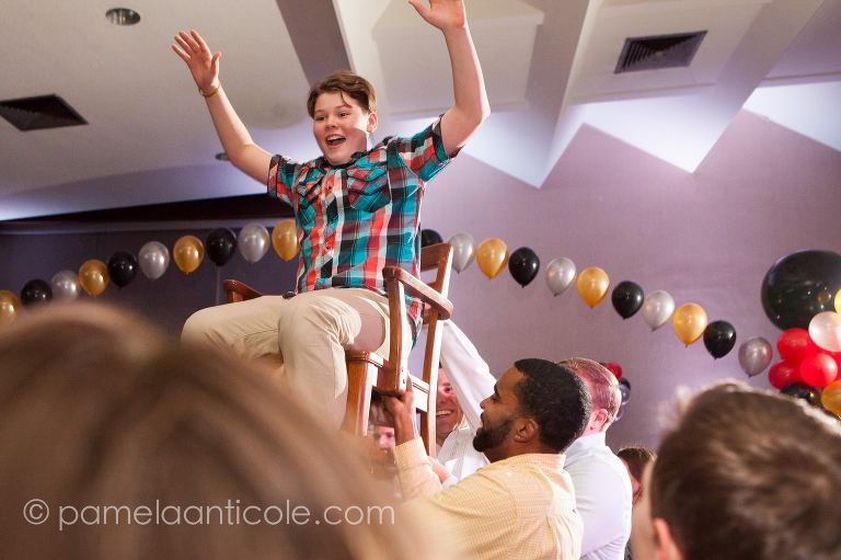 mitzvah boy goes up on a chair at a party, surrounded by friends and family and balloons