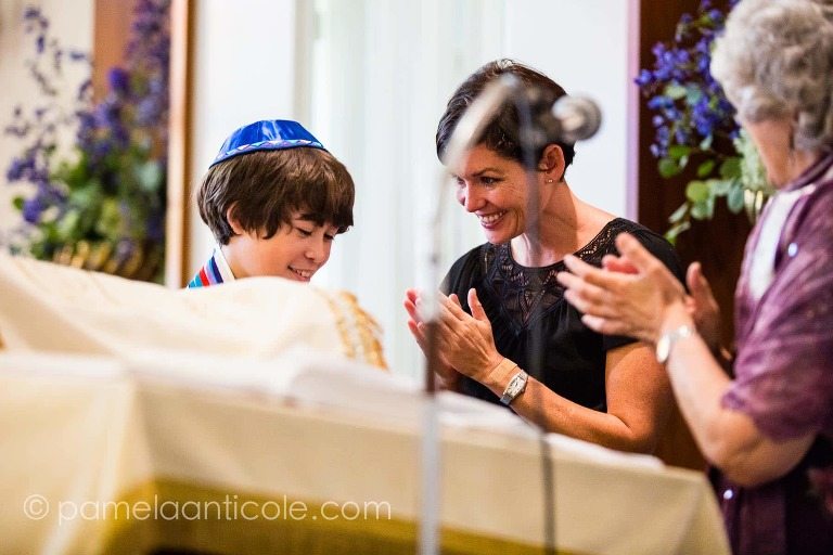 candid photo of a mom smiling down at her bar mitzvah son during his mitzvah ceremony