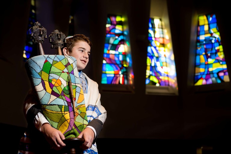 bar mitzvah boy stands holding the torah in front of some stained glass windows.