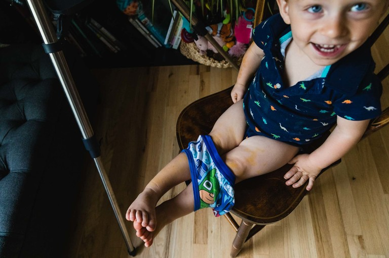 toddler trying on underwear and laughing proudly.