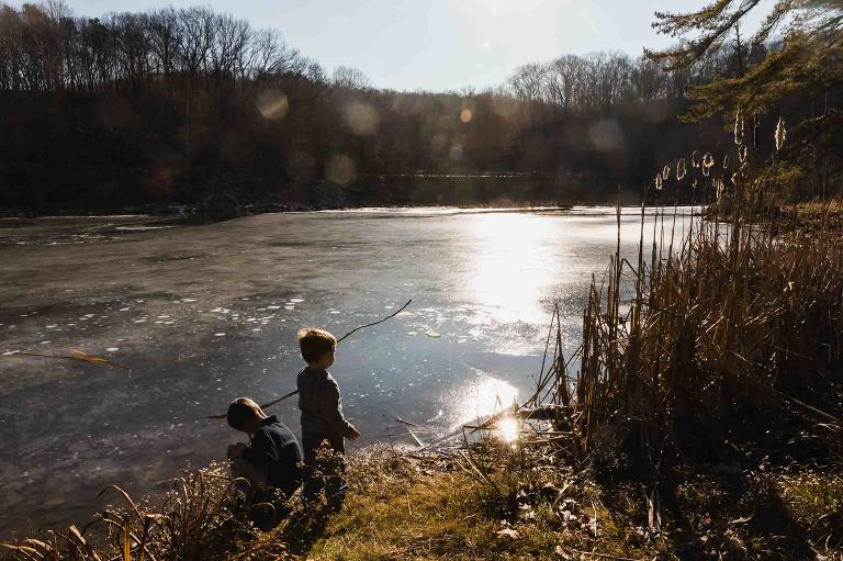 two young boys playing in the park in front of a lake, pretending to fish with sticks.