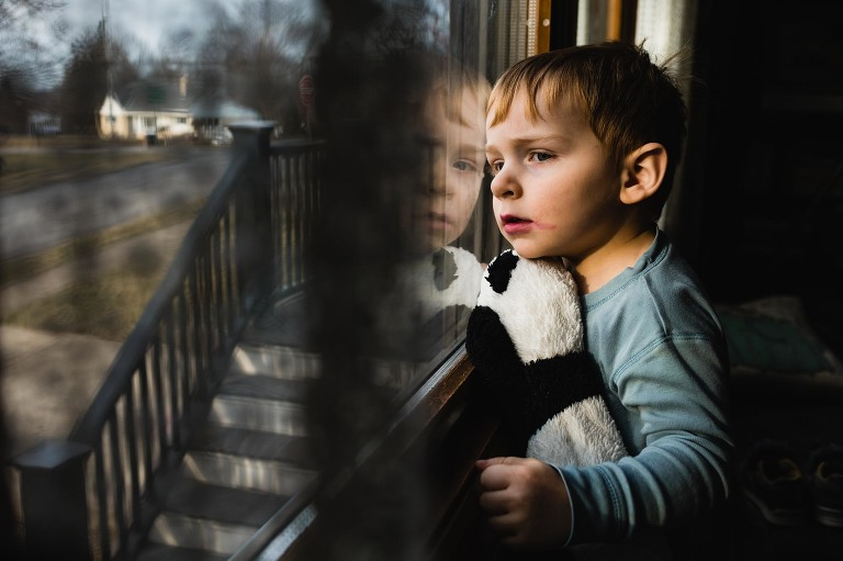 boy sits at the window with smeared lipstick and panda bear stuffed animal, looking out the window