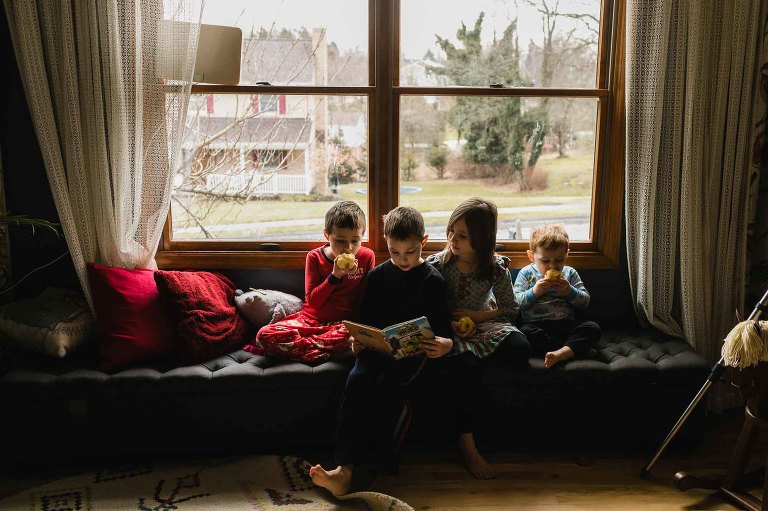 kids sit together in a window seat, reading and eating apples
