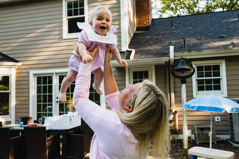 baby girl laughing, being held up into the air by her mama for family pictures