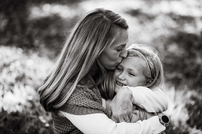 black and white photo of mom hugging and kissing little girl