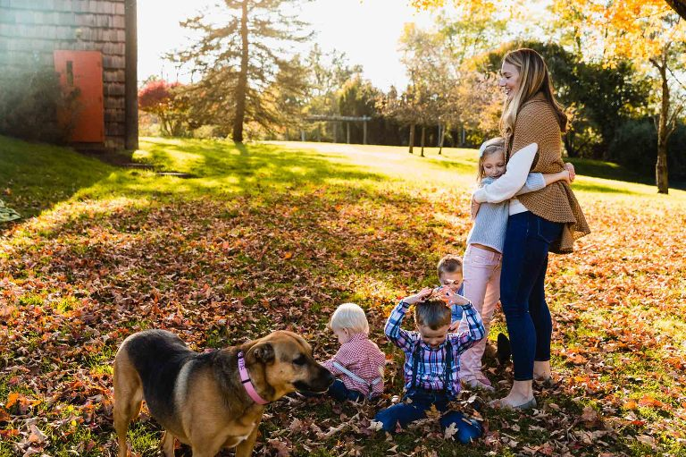 mom snuggling with her little girl while the boys play in the leaves with the dog, during their family photo session in pittsburgh