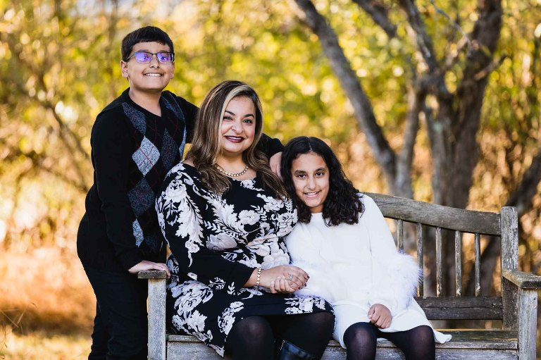 mom sits with her kids in a bench for a family portrait in the fall in pittsburgh