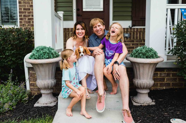 picture of laughing family in front of their home for a front porch session