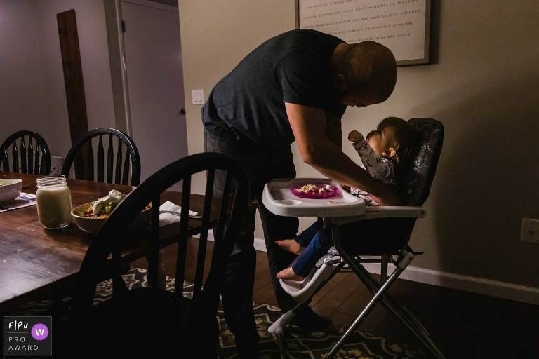 award winning fpja image of little girl in highchair reaching up for her dad who is unbuckling her