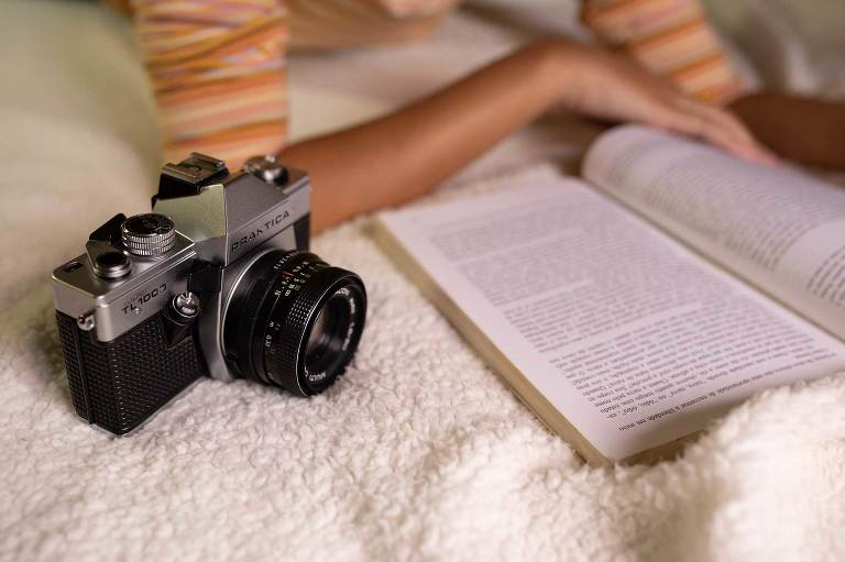 black slr camera lying beside an open photography book that a woman is reading