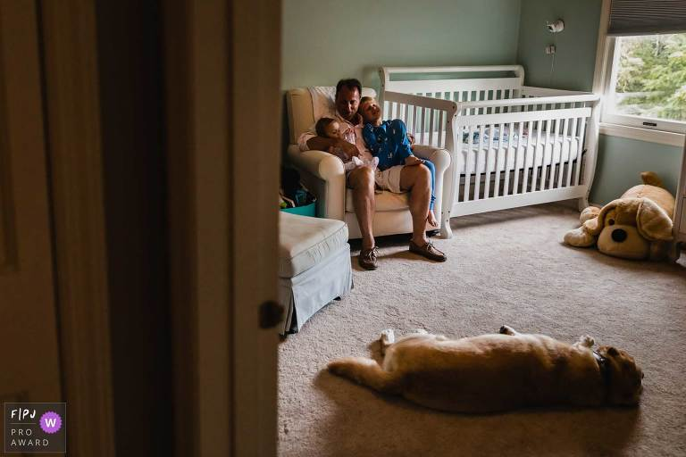 image of dad sitting in nursery holding baby and big brother, while big stuffed dog and real dog lay around