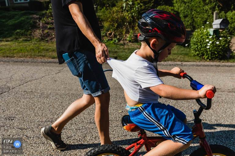 image of little boy riding a bike while mom holds his shirt and walks alongside him