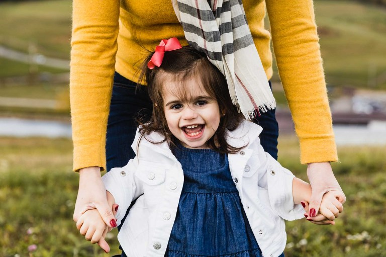 little girl with pink bow and white jacket holding onto her mom's hands (wearing a yellow sweater) and smiling ear to ear