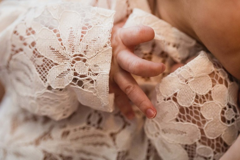 color closeup of newborn baby girl's nails, wrapped in lace onesie