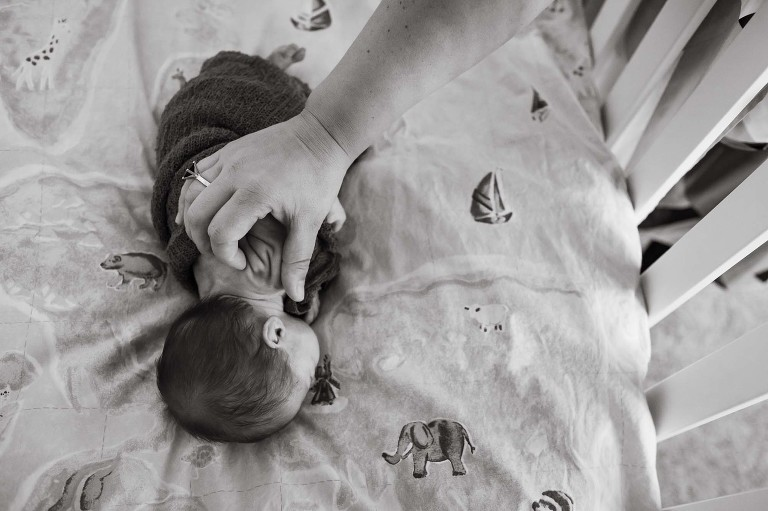 black and white photo of baby girl lying in crib with mom petting wrinkles on her back