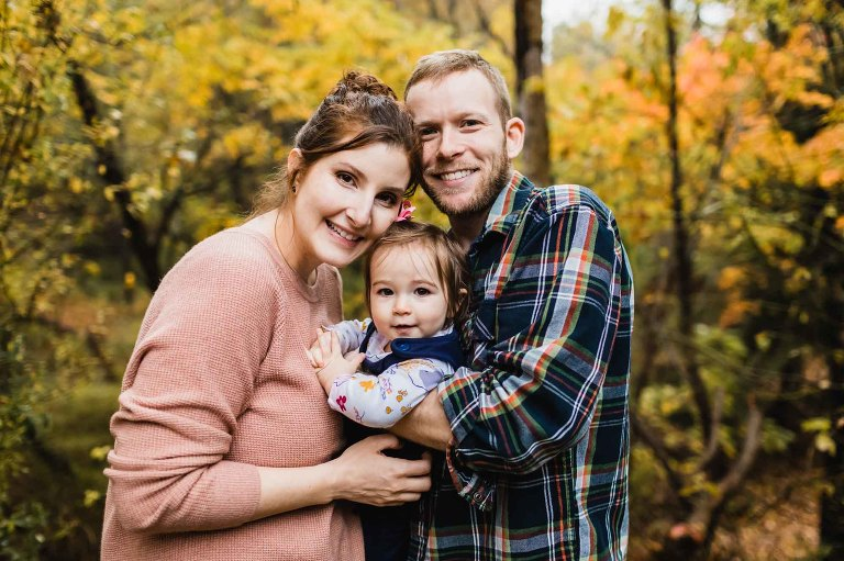 mom and dad holding baby girl for a lifestyle family portrait in front of fall foliage