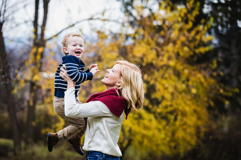 mom holds laughing toddler up into the air, in front of yellow fall foliage