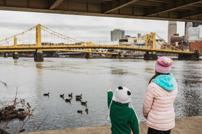 kids watching the geese cross the river, in front of the yellow bridges of pittsburgh