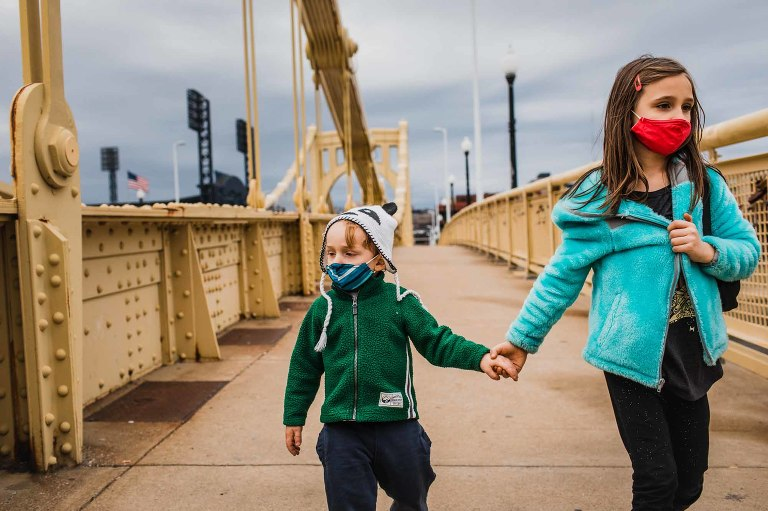 little girl holds her baby brother's hand as they cross the yellow bridge in pittsburgh