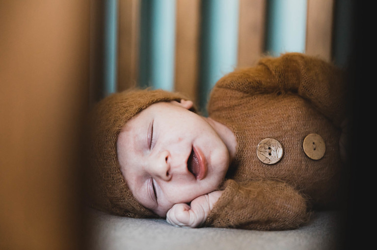 sleeping baby smiles in crib, bundled up in adorable brown onesie with wood buttons and hat