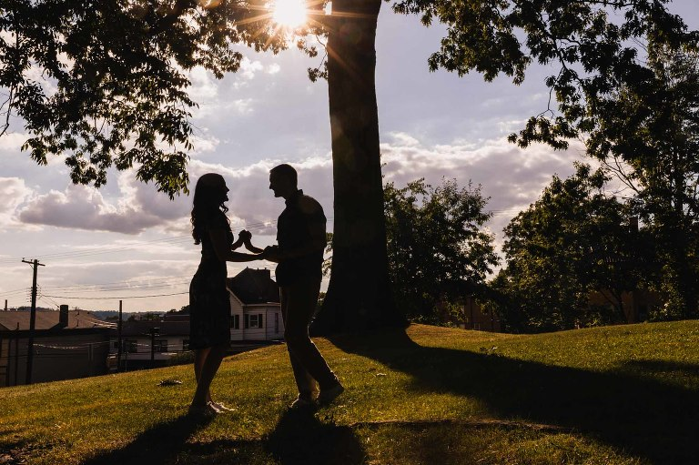 silhouette of man and woman holding hands in a city park, framed by a tree