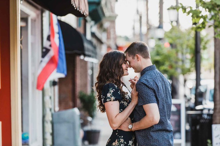 man and woman with foreheads together, snuggling together sweetly with hands intertwined, on an empty city street