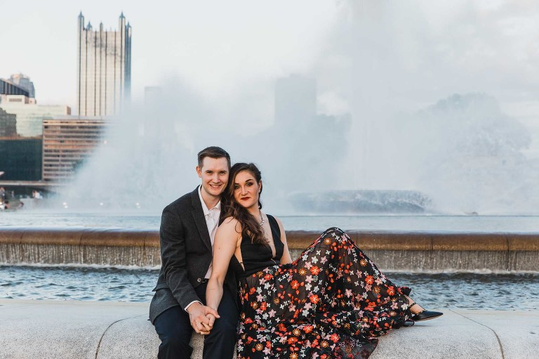 bride and groom snuggled together in front of the fountain at point state park in downtown pittsburgh