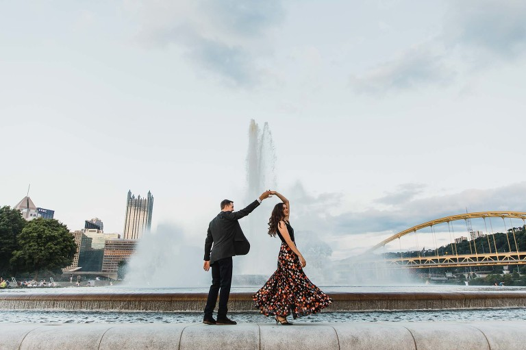 man twirling woman in front of a tall fountain, with the pittsburgh city and bridge backdrop behind them. at sunset