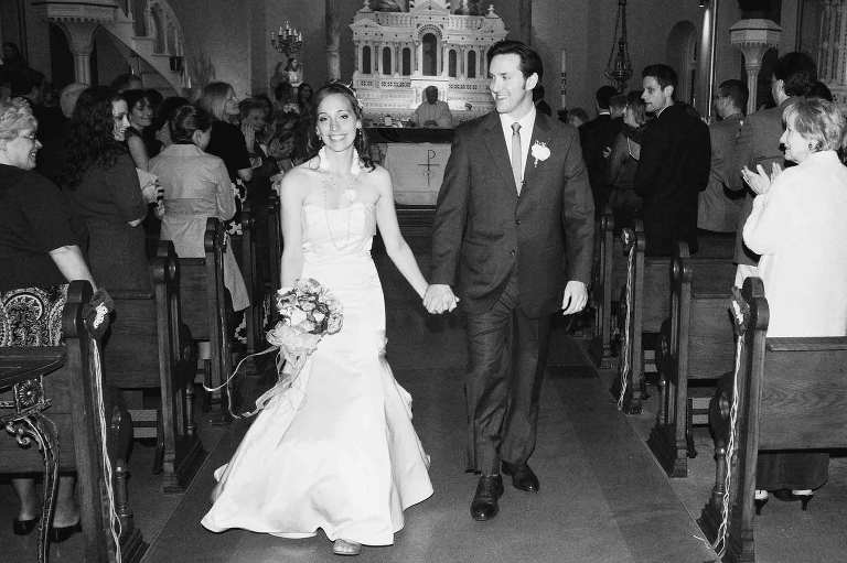 bride and groom exit church holding hands and smiling, in black and white