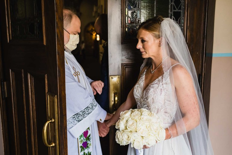 bride and groom stand behind a door away from each other before the ceremony, while priest blesses them in the church