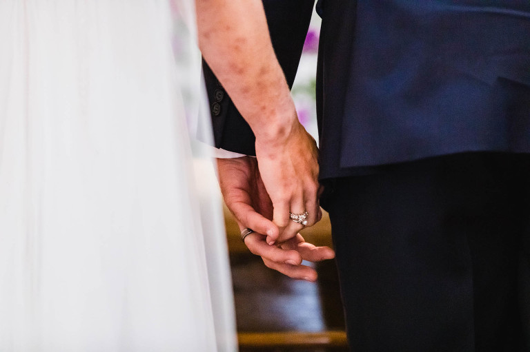bride and groom's hands gently touching each other during their wedding ceremony