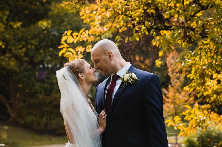 bride and groom gazing into each others eyes, noses together, under fall leaves in the afternoon sun on chatham campus