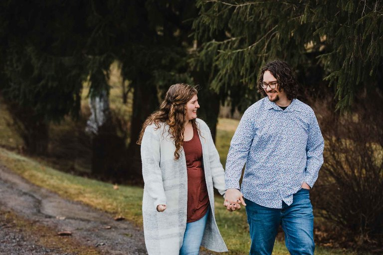 young couple walk together in the winter outside along a tree lined path