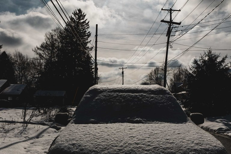 found still life of car covered in snow, in the street, with the sun shining and the clouds out